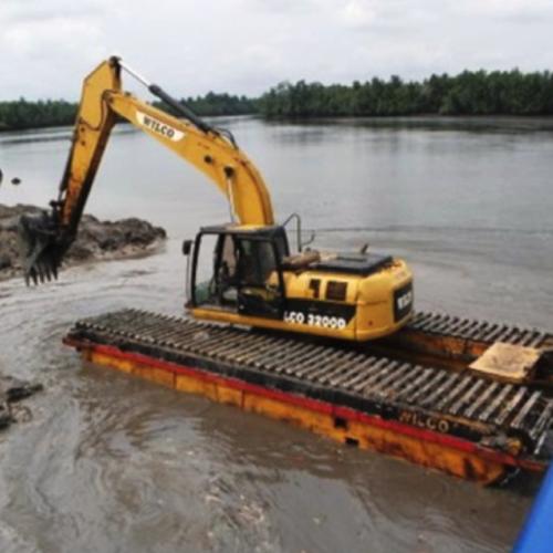עבודה עם באגר באזור ביצתי – תמונה זו מדגימה את האתגר בעבודה בסמוך לנהר